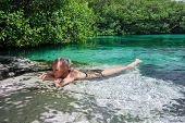 pic of cenote  - Beautiful woman floating in a nature swimming pool - JPG