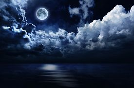 stock photo of moonlight  - Clouds and water illuminated by soft moonlight from a full moon - JPG