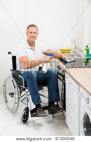 Man On Wheelchair Cleaning Induction Stove