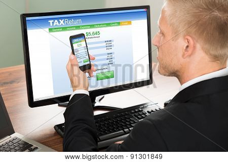Businessman Looking At Online Tax Return Form