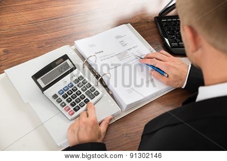 Businessman Calculating Invoice At Desk In Office