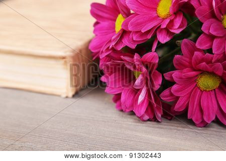Beautiful flowers with book on wooden table, closeup