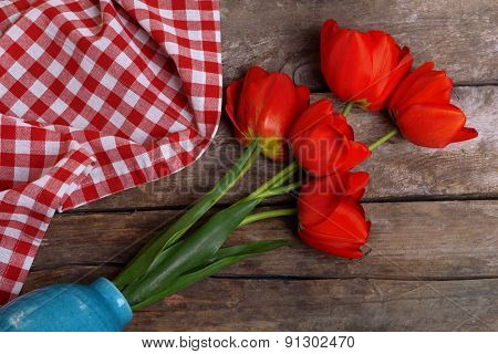 Red tulips in vase on wooden background top view