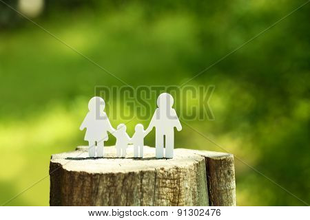 Cutout family on stump on blurred background