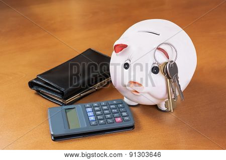 Piggy Bank, Calculator, Keys  And Purse On Wood Table