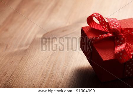 Red Gift Box Tied Red Ribbon On Wooden Table