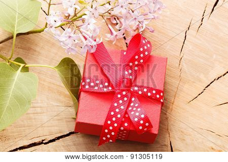Red Gift Box Tied Red Ribbon And Flowers On Wooden Background