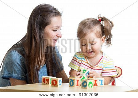 child girl and mom have fun playing cubes toys