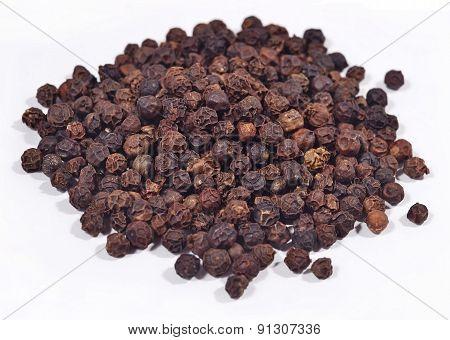 Heap Of Black Pepper On A White