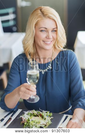 people, holidays and lifestyle concept - happy smiling woman drinking champagne at restaurant