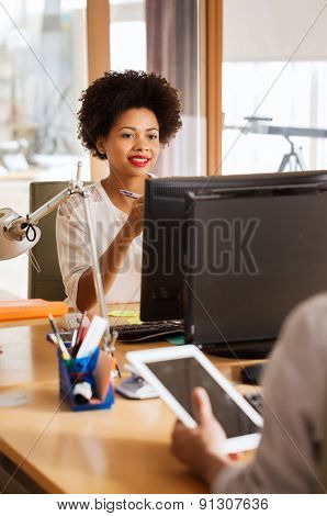 business, startup and people concept - happy businesswoman or creative female office worker with computer and telephone sitting at table