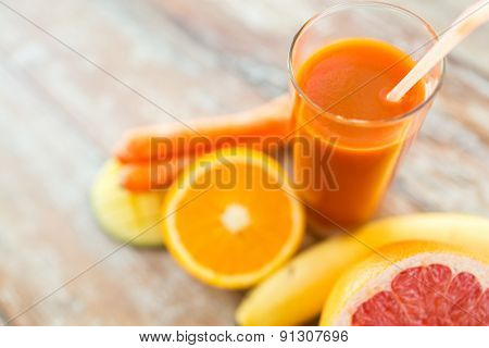 healthy eating, food and diet concept - close up of fresh juice glass and fruits on table