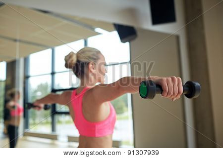 fitness, sport, training, people and lifestyle concept - woman with dumbbells flexing muscles in gym