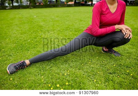 fitness, sport, training, people and lifestyle concept - close up of woman stretching leg and doing lunge in park