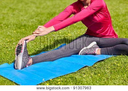fitness, sport, training, people and lifestyle concept - close up of woman stretching leg on mat in park