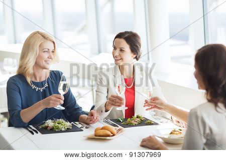 people, holidays, celebration and lifestyle concept - happy women drinking champagne at restaurant