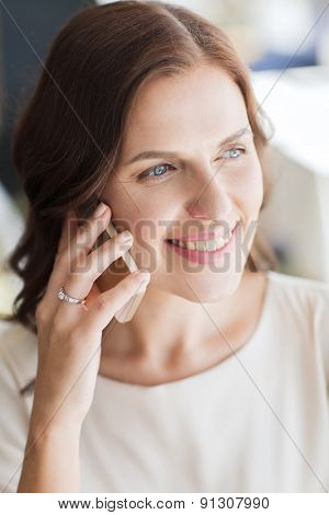 people, women, business and lifestyle concept - happy woman calling on smart phone at restaurant