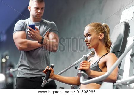 sport, fitness, bodybuilding, teamwork and people concept - young woman and personal trainer flexing muscles on gym machine
