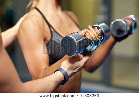 fitness, sport, bodybuilding and weightlifting concept - close up of young woman and personal trainer with dumbbells flexing muscles in gym