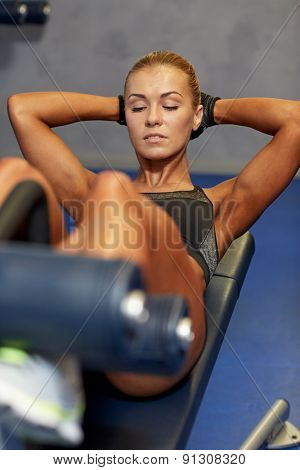 fitness, sport, training and lifestyle concept - woman flexing abdominal muscles on bench in gym