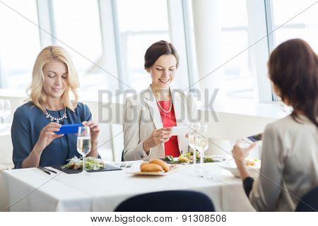 people, holidays, technology and lifestyle concept - happy women with smartphones taking picture of food at restaurant