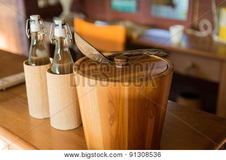 tableware and kitchenware concept - couple of bottles and wooden bucket with spoon on table at hotel room