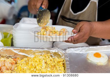 cooking, asian kitchen, sale and food concept - close up of hands with plate, spoon and wok at street market