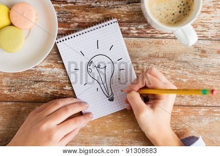 business, education and people concept - close up of female hands with pencil, coffee and cookies drawing lighting bulb to notebook on table