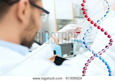 science, chemistry, biology, medicine and people concept - close up of male scientist with test tube and pipette making research in clinical laboratory