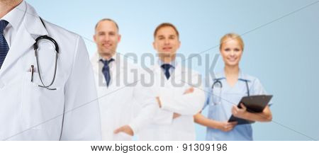 healthcare, profession, teamwork and medicine concept - group of happy medics in white coats over blue background