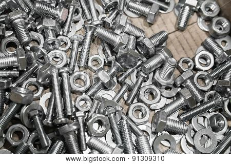 Shining Bolts And Nuts In A Cardboard Box