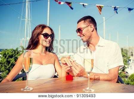 love, dating, people and holidays concept - smiling couple wearing sunglasses with champagne and small red gift box putting wedding ring on finger at cafe