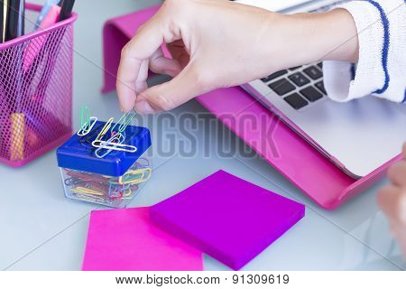 Female Hand Taking A Paperclip.