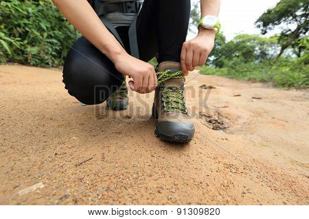 woman hiking tying shoelace on forest trail