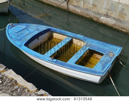 A rowing boat with a lot of rain water