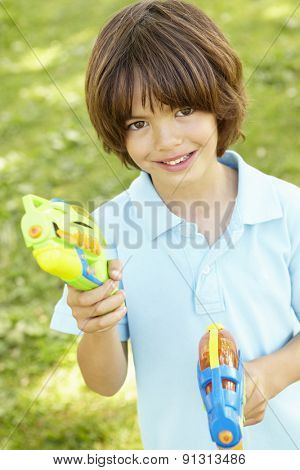 Young Boy Playing With Water Pistols In Park