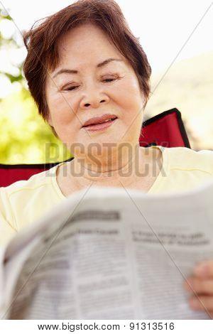 Senior Asian woman reading outdoors