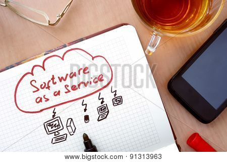 Notepad with word SaaS software as a service concept.