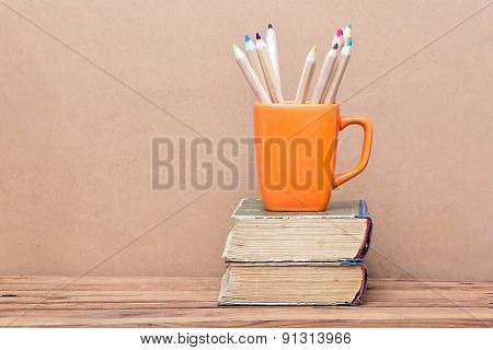 Books Tower And Orange Mug With Colored Pencils