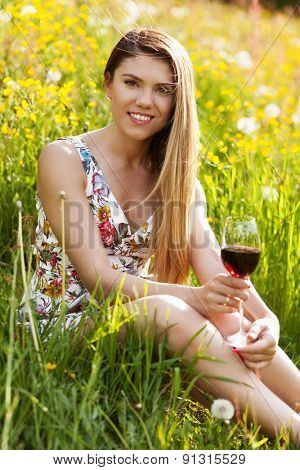 Young beautiful woman drinking wine outdoors.