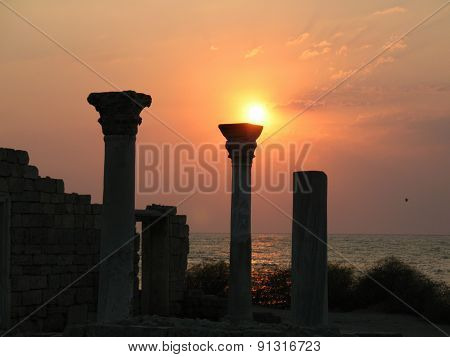 Columns of the temple of the ancient Greek colony at sunset in Hersonissos