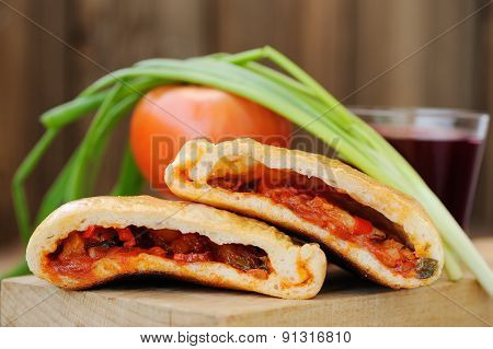 Two Pieces Of Pizza Calzone With Glass Of Red Wine, Fresh Scallion And Tomato On Wooden Board