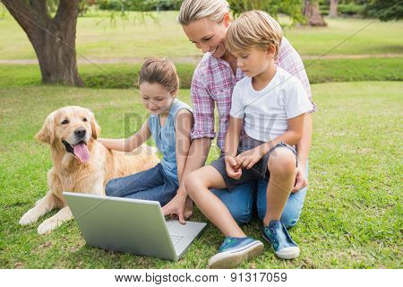 Happy family with their dog using laptop on a sunny day