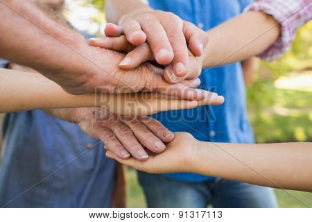 Family putting their hands together on a sunny day