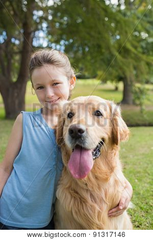 Little girl with her dog in the park on a sunny day