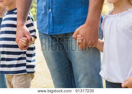 Family holding their hands on a sunny day