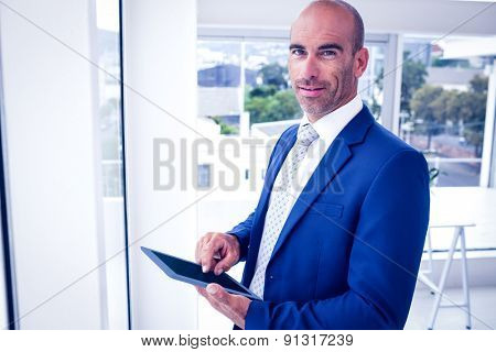 Businessman using his tablet pc in his office