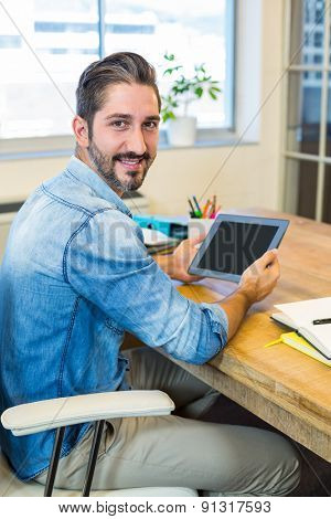 Casual businessman working at his desk with tablet in the office