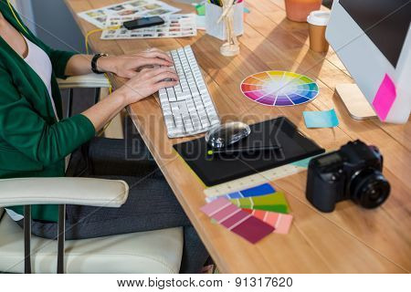 Designer typing on keyboard in the office