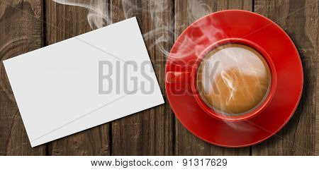 Red cup of coffee against white card